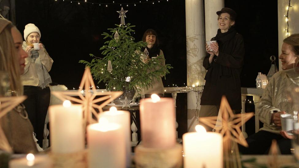 Kynttilöitä etualalla, viisi naista mukit kädessä takana